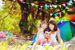 Happy young family with child resting outdoors in summer park Stock Photos