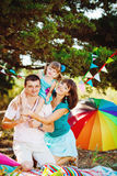 Happy young family with child resting outdoors in summer park Stock Photography