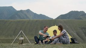 Happy young family with a child resting together in front of a tent in the mountains and drinking tea from a thermos stock footage