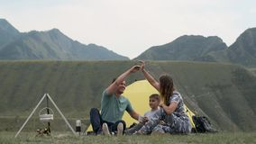 Happy family with a child resting together in front of a tent in the mountains, smiling and having fun. concept stock video footage