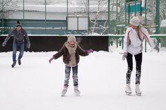 Happy young family with child skate at the outdoor ice rink in the winter. Beautiful family walking and playing on the ice in stock photos