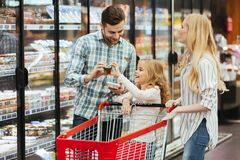 Happy young family with a child standing with a trolley. And choosing food at supermarket Royalty Free Stock Image