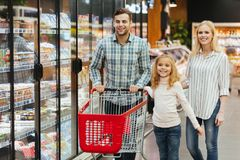 Happy young family with a child walking with a trolley. At supermarket Stock Photos