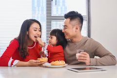 Happy young family with children enjoying breakfast in a white sunny dining room with a big garden view window royalty free stock photos