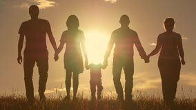 Happy young family with children running around the field, silhouette at sunset. Happy young family with children running around the field Royalty Free Stock Photo