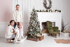 Happy young family in Christmas morning in home. look at the camera. Happy new year Royalty Free Stock Photo