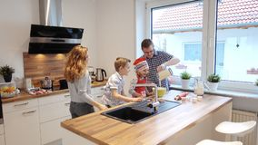 Happy young family cooking and having fun in the morning at kitchen stock photography
