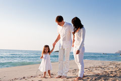 Happy young family with daughter on beach in summer Royalty Free Stock Photos