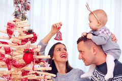 Happy young family decorate eco christmas tree at home Royalty Free Stock Images