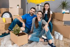 Happy young family dismantles cardboard boxes and makes home improvement. stock photography