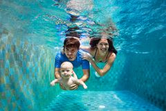 Happy young family dive underwater in swimming pool Stock Photos