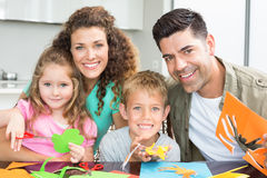 Happy young family doing arts and crafts at the table Stock Image