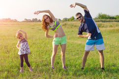 Happy young family doing exercises outdoors. Mom, Dad and daughter, sports family. royalty free stock photo