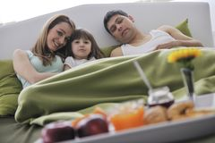 Happy young family eat breakfast in bed Stock Photography