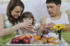Happy young family eat breakfast in bed Stock Photos