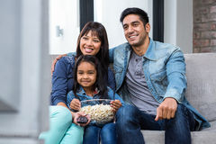 Happy young family eating popcorn while watching tv. In living room Royalty Free Stock Photography