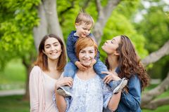 Happy young family enjoying free time in the park, mother, sisters and brother Stock Photography