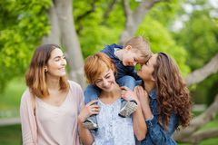 Happy young family enjoying free time in the park, mother, sisters and brother Royalty Free Stock Photography