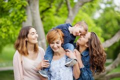 Happy young family enjoying free time in the park, mother, sisters and brother Royalty Free Stock Photo
