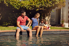 Happy young family enjoying near pool. Happy young couple sitting on the edge of swimming pool with their kids enjoying a hot summer day near pool. Couple's feet Stock Photos