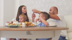 Happy young family enjoying tea with sweets at restaurant or cafe or home stock video
