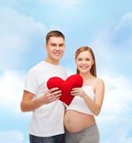 Happy young family expecting child with big heart Royalty Free Stock Images