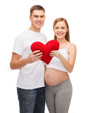 Happy young family expecting child with big heart Stock Image