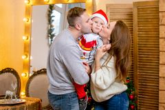 Happy young family, father, mother and son, in Christmas evening in home. They kisses his son. New Year`s and Christmas theme. Holiday mood royalty free stock images