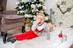 Happy young family, father, mother and son, in Christmas evening in home. A little boy is sitting on the floor near the tree with royalty free stock image