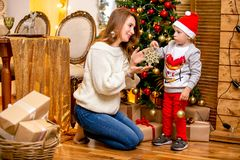 Happy young family, father, mother and son, in Christmas evening in home. Mom and son decorate Christmas tree. New Year`s and. Christmas theme. Holiday mood stock photos