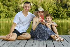 Happy young family, father mother and two little sons are sitting and taking selfies on the river pier stock images