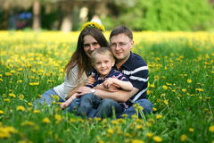 Happy young family on field of dandelions Royalty Free Stock Image
