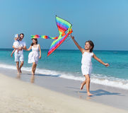 Happy young family with flying a kite. On the beach royalty free stock image