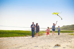 Happy young family with flying a kite on the beach. Summer vacation stock photo