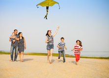 Happy young family with flying a kite on the beach Stock Photos