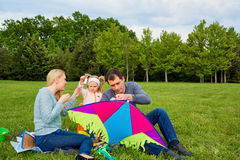 Happy young family with flying a kite in the park. Stock Photo
