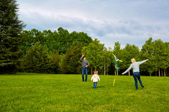 Happy young family with flying a kite in the park. Stock Images