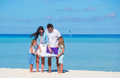 Happy young family of four with map on the beach Royalty Free Stock Images