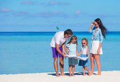 Happy young family of four with map on the beach Stock Photos