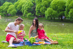 Happy young family of four picnicking near the Stock Image