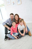 Happy young family of four sitting on the house floor Stock Image