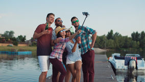 Happy young family or friends taking a selfie. Happy young family or group of friends taking a selfie together on a wooden jetty at a lake while holding beers on stock photo