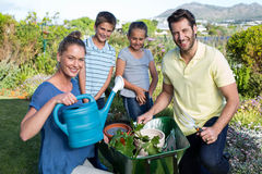 Happy young family gardening together Stock Photos