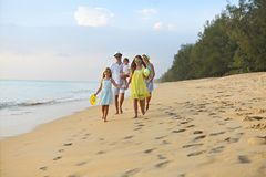 Happy young family have fun on beach run and jump. At sunset stock images
