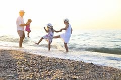 Happy young family have fun on beach run and jump. At sunset stock photo