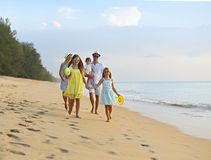 Happy young family have fun on beach run and jump. At sunset stock photos
