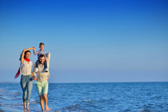Happy young family have fun on beach run and jump at sunset.  stock photo