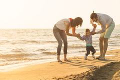 Happy young family have fun on beach run and jump at sunset Stock Photography