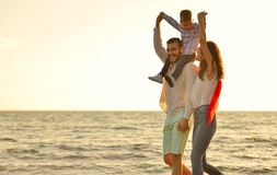Happy young family have fun on beach run and jump at sunset Stock Photos