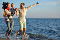 Happy young family have fun on beach run and jump at sunset.  stock image